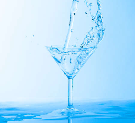 Water Splashing in a Wineglass, on blue background photo