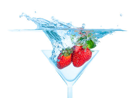 Fresh Strawberry Dropped into Glass with Splash on white backgrounds photo