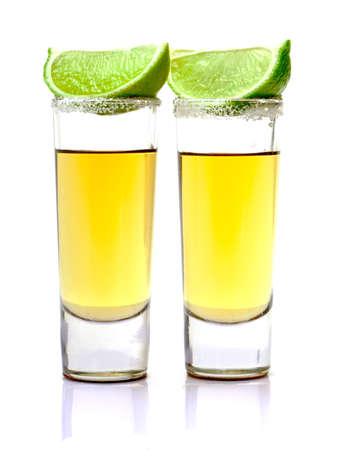 Shot of Gold Tequila with Slice Lime on white background photo