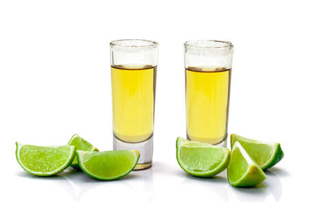 Shot of Gold Tequila with Slice Lime on white background Фото со стока