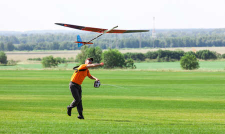 Man launches into the sky RC glider, on grass field photo