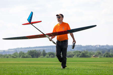 Man holds the RC glider, on grass field photo
