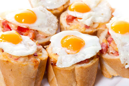entree: Baguette Slice with Ham and Fried Quail Egg, closeup Stock Photo