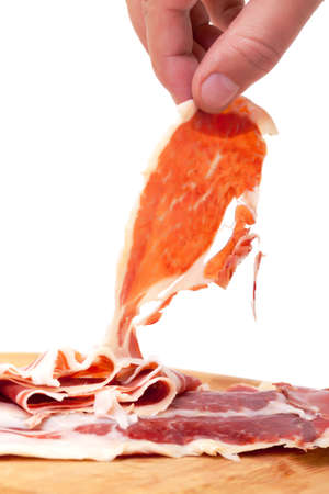 Thinly Sliced Spanish Jamon with a Hand, on a white background