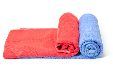 absorbent: Two thick absorbent rolled red and blue bath towels on white background conceptual of health, hygiene and a spa treatment