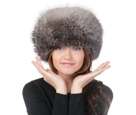 Glamorous woman in winter fashion standing with her hands raised to her fur hat isolated on white Stock Photo - 15834694