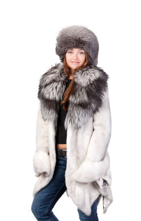 Sexy woman wearing a stylish winter fur coat and hat for protection against the bitter cold on a white background photo