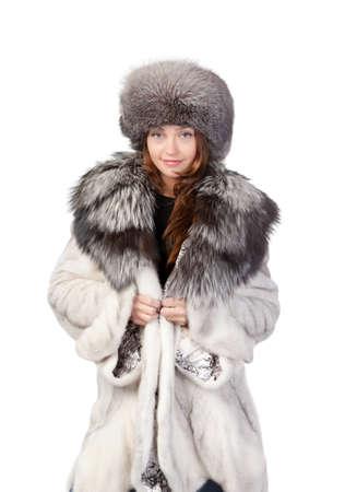 bontjas: Sexy vrouw het dragen van een stijlvolle winter bontjas en hoed voor bescherming tegen de bittere kou op een witte achtergrond Stockfoto