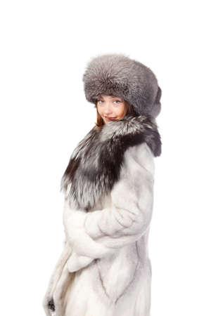 Sexy vrouw het dragen van een stijlvolle winter bontjas en hoed voor bescherming tegen de bittere kou op een witte achtergrond Stockfoto