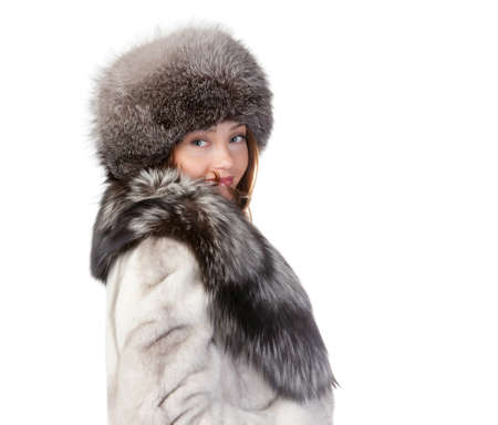 Sexy woman wearing a stylish winter fur coat and hat for protection against the bitter cold on a white background Stock Photo - 15834683