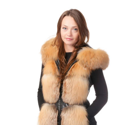 Stylish relaxed young woman in winter fur jacket standing with her hands in her pocket isolated on white Stock Photo - 15834698
