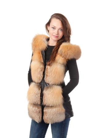 Stylish relaxed young woman in winter fur jacket standing with her hands in her pocket isolated on white Stock Photo - 15834687