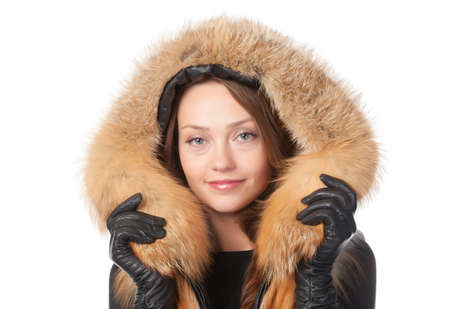 Beautiful smiling woman in fur trimmed jacket with hood keeping warm against the winter cold isolated on white photo