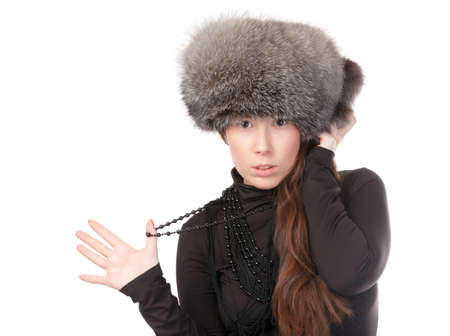 Vivacious woman in a winter outfit with a fur hat on white background photo