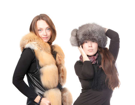 Two attractive women dressed for winter posing together on a white background in fur trimmed garments photo