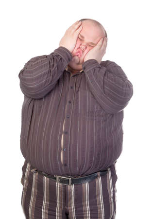 Obese man standing squashing his face with his hands with his buttons popping open over his huge belly isolated on white Фото со стока