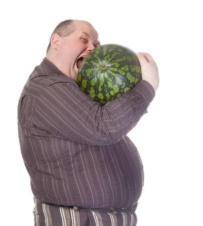 hambriento: Hombre obeso con un vientre enorme tratando de morder una sand�a como su apetito insaciable saca lo mejor de �l antes de que se puede cortar, parodia humor�stica sobre blanco Foto de archivo