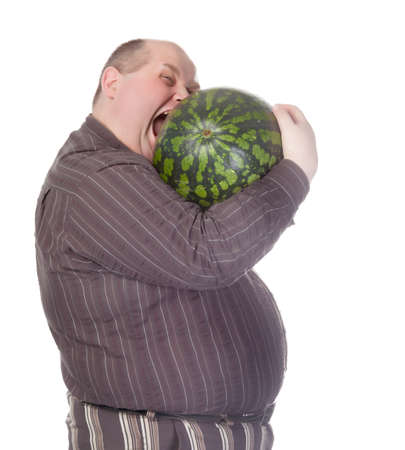 greedy: Obese man with a huge belly attempting to bite into a watermelon as his insatiable appetite gets the better of him before he can cut it, humorous spoof on white Stock Photo