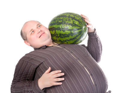 contemplates: Obese man carrying a watermelon on his shoulder and rubbing his belly with a gleeful look of anticipation as he contemplates the delights of devouring it Stock Photo