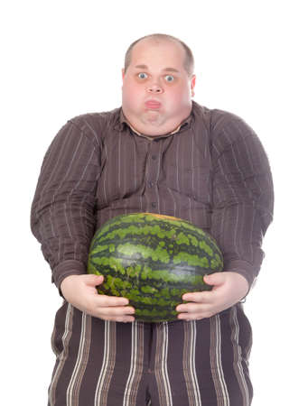straining: Humorous image of an unfit obese man struggling to hold the weight of a whole watermelon held at arms length in front of his huge protruding belly, isolated on white Stock Photo