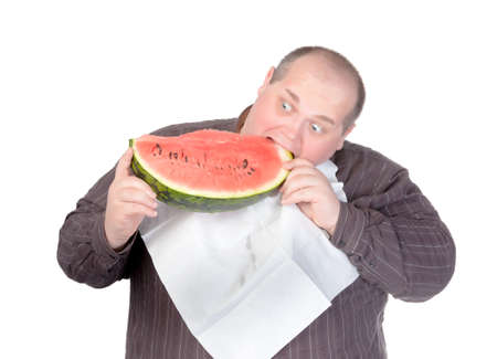 Fat man with a serviette around his neck as a bib tucking into a large slice of fresh juicy watermelon with a look of anticipation and glee isolated on white