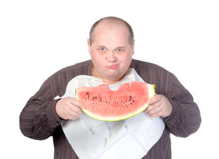 Obese man with a serviette bib around his neck standing eating a large slice of fresh juicy watermelon isolated on white photo