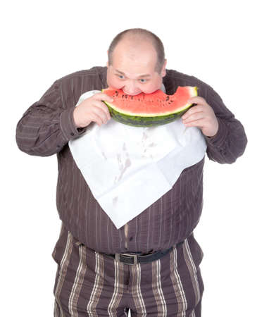 glutton: Obese man with a serviette bib around his neck standing eating a large slice of fresh juicy watermelon isolated on white Stock Photo