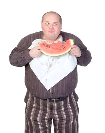Obese man with a serviette bib around his neck standing eating a large slice of fresh juicy watermelon isolated on white Stock Photo