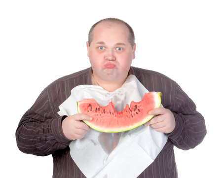 serviette: Obese man with a serviette bib around his neck standing eating a large slice of fresh juicy watermelon isolated on white Stock Photo