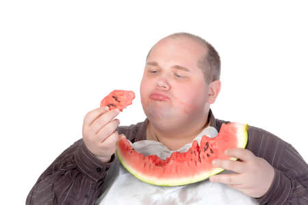 Fat man savouring a slice of watermelon holding a chunk in his hand and looking at it with satisfaction and relish isolated on white photo
