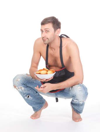 delantal: Hombre atractivo intentar su mano en la que llevaba un delantal de hornear y llevar un plato de galletas reci�n horneadas aislados en blanco Foto de archivo
