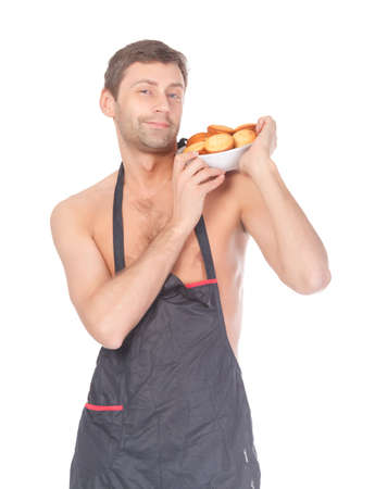 Attractive man trying his hand at baking wearing an apron and carrying a bowl of freshly baked cookies isolated on white
