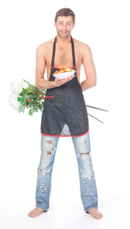 Humorous image of a handsome shirtless man barefoot and in ragged jeans wearing an apron and carrying flowers and cookies as a Valentines or anniversary gift photo