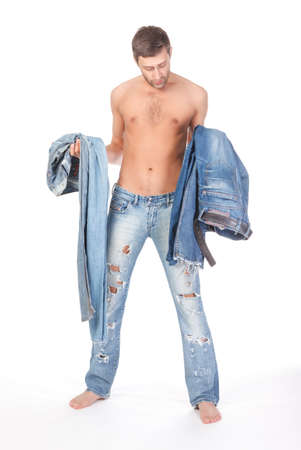 Cool shirtless trendy man in a pair of modern ragged jeans standing deciding what to wear with two pairs of denims in his hands photo