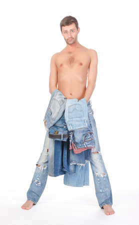 ambivalent: Cool shirtless trendy man in a pair of modern ragged jeans standing deciding what to wear with two pairs of denims in his hands