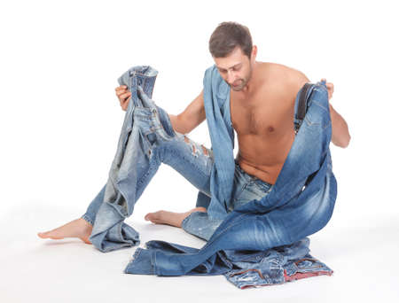 man in jeans: Cool shirtless trendy man in a pair of modern ragged jeans sitting deciding what to wear  Stock Photo