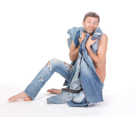 Attractive Indecisive man trying to dress sitting shirtless and barefoot on the floor holding several pairs of denim jeans shrugging his shoulders with a look of consternation photo