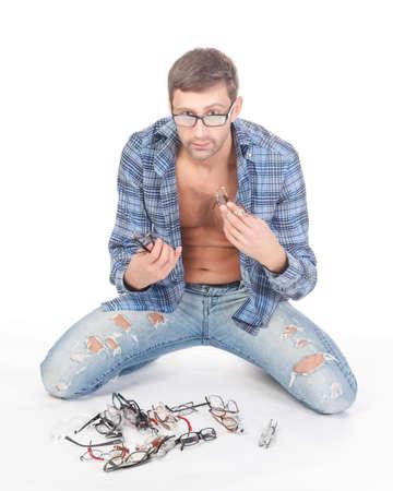 alkalmasság: Alkalmi divat tudatos jóképű férfi próbál a különböző üvegek bálából a földön előtte fehér háttér stúdióban