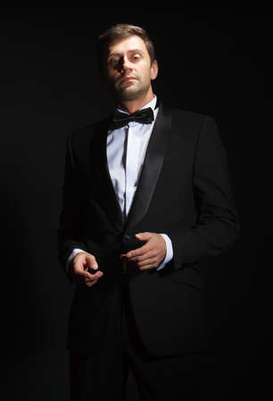 Dramatic portrait of a suave handsome man in a tuxedo and bowtie highlighted in darkness photo