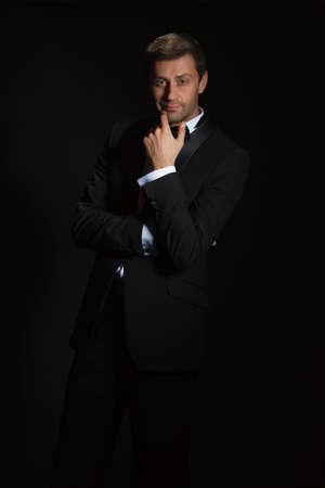 playboy: Dramatisch portret van een suave knappe man in een smoking en bowtie gemarkeerd in het donker Stockfoto
