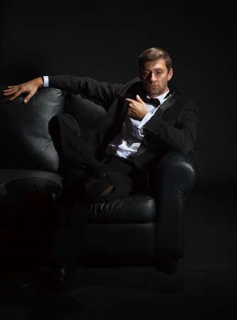Drámai portré egy kedves jóképű férfi szmoking és bowtie a kanapén kiemelt sötétben Stock fotó