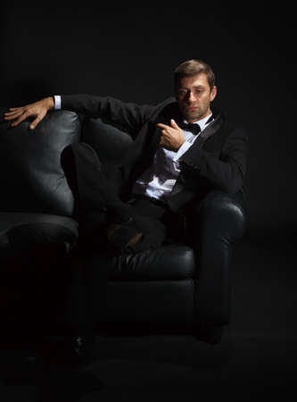 jilted: Dramatic portrait of a suave handsome man in a tuxedo and bowtie on couch highlighted in darkness