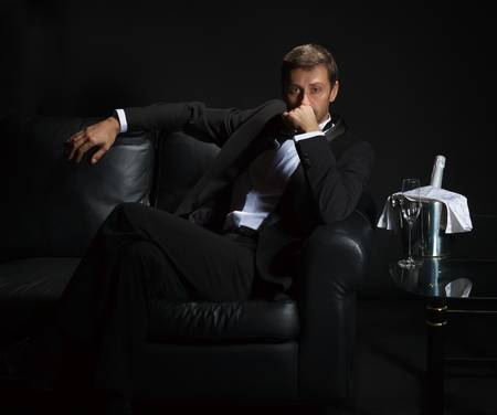 Sexy handsome man in tuxedo sitting in the darkness of a nightclub with an unopened bottle of champagne on ice waiting for his date photo