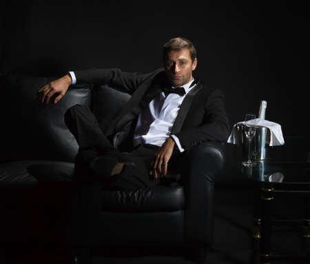Sexy przystojny m??czyzna w smokingu siedzi w ciemno?ci nocnego klubu z zamkni?tym butelk? szampana na lodzie czekaj?c na dzie? Zdjęcie Seryjne