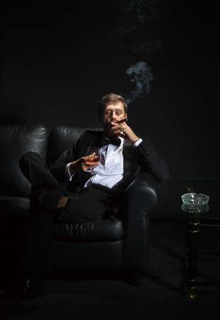 fumando: Macho man con un esmoquin elegante sentado en la oscuridad en un club nocturno fumando un puro y bebiendo brandy o co�ac Foto de archivo