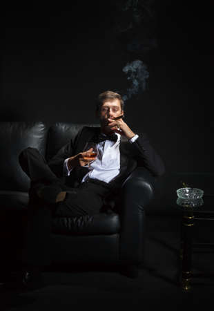 Macho man in a stylish tuxedo sitting in the darkness at a nightclub puffing on a cigar and drinking brandy or cognac photo