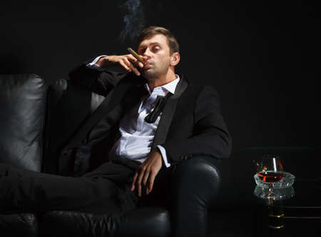 Macho man in a stylish tuxedo sitting in the darkness at a nightclub puffing on a cigar and drinking brandy or cognac Stock Photo - 15896975