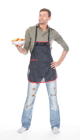Attractive man trying his hand at baking wearing an apron and carrying a bowl of freshly baked cookies isolated on white photo