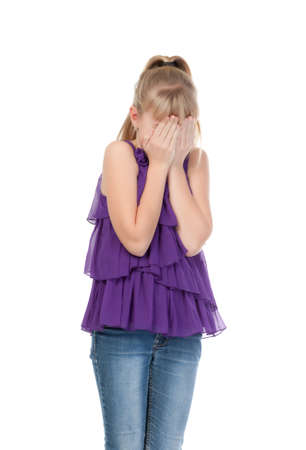11 year old: Young girl shyly covered her face with her hands, isolated on white background