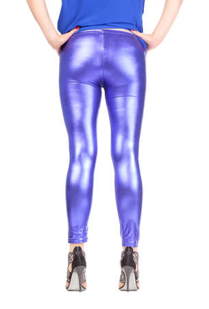 Cropped view image of a womans sexy legs and buttocks clad in shimmering blue leggins and stilettos in a seductive stance with her back to the camera photo